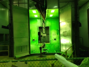 Here, large no-till air drill components go into the green paint booth where workers in space suits apply special electrostatic-charged green powder that is subsequently baked on to become that famous green.