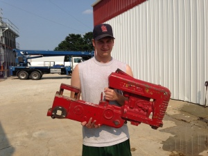 Ben holds half the pedal tractor, you can see it's early in the restoration process.