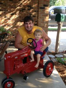 Although her feet don't reach the pedals, Ella can steer the tractor while daddy pushes.