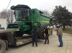 The guys begin to loosen the tie-down chains so that the new combine can be driven forward onto the ground at Carnahan & Sons.