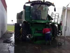 John works on cleaning the S680 combine on a warmer but windy morning.