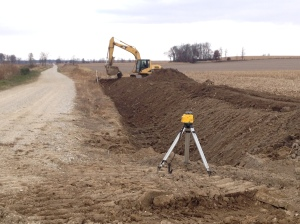 "This new channel being carved along the gravel road will re-direct the water coming from above...water will no longer flow out into this field, but remain along the road.  See the laser generator on the tripod?  Beneath that is the opening to a newly-installed 30"" x 100' culvert that creates a new entrance to the field.  The culvert pipe creates a new field entrance."