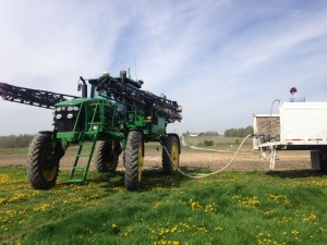 John works in the back of the water trailer, mixing his recipe of herbicides and wetting agents into a funnel-shaped inductor... then the blend is pumped into the JD 4730 sprayer with the water.  One ingredient is Roundup, another is Sharpen, which goes on the field at the rate of 1 oz/acre.