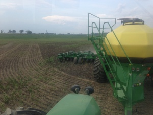 Looking back from the tractor cab, you can see that the soybean planter is placing the seed into the soil in nearly-ideal conditions today.  Look! There's even some dust from the soil surface being kicked up by this planting operation!