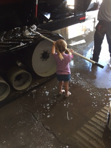 Ella helped her daddy wash up the Demco 1350 grain cart.