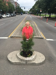 Pat stands on the 'world's smallest city park, Mill Ends Park in Portland