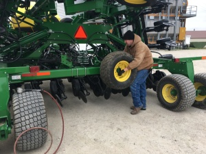 Here, John installs the spare wheel and tire to the back of the soybean air drill